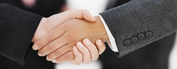 Close-up of the hands of two businesswomen shaking hands with two businessmen in background --- Image by © Royalty-Free/Corbis